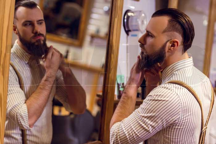 barbudo olhando no espelho com sua barba cheia